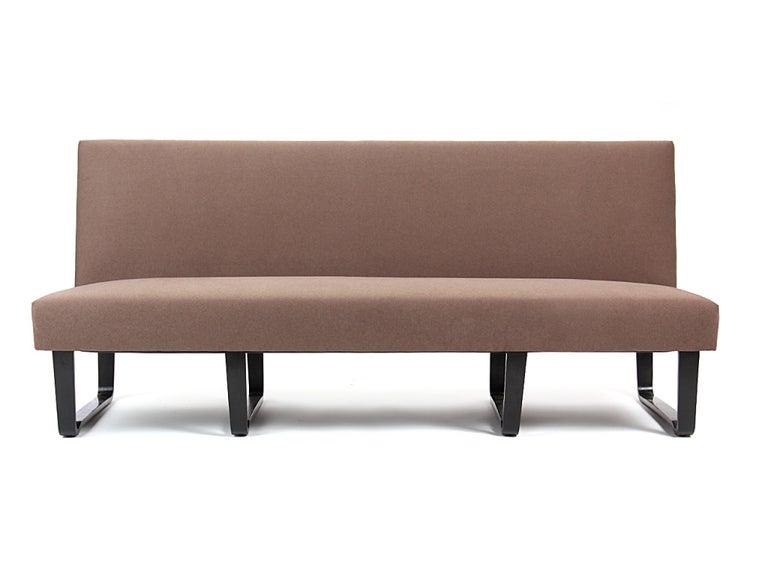 An armless sofa or bench or banquet on laminated mahogany