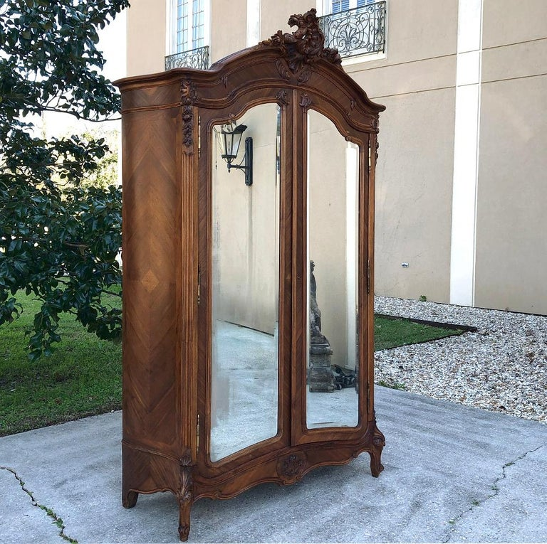 19th century French Louis XV walnut armoire exudes the Classic lines of the rococo movement, with asymmetrical shell, floral and foliate carving atop the boldly arched crown. The scrollwork and exquisite carved embellishment of the apron and legs