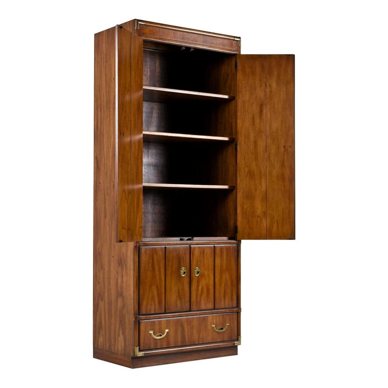 Solid wood Campaign style corner cabinet curio bookshelf made by esteemed US furniture maker Drexel Heritage in the 1970s. Faux bamboo brass corner accents on all four corners and brass pull hardware tie together British traditional and Eastern
