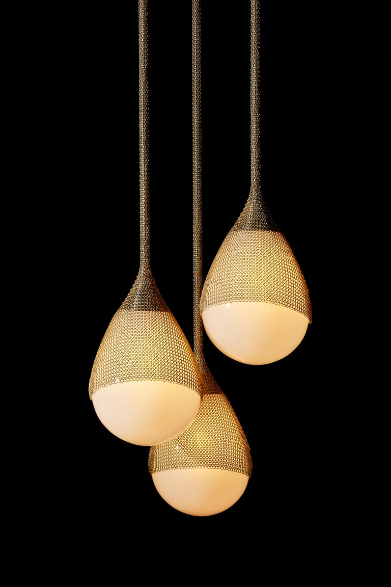 Part of the Armor collection, the Armor Triple cluster pendant features three hand blown glass fixtures draped with finished chainmail. Pulling from the intricate use of chainmail in Medieval armor, we reinterpret its materiality by creating a