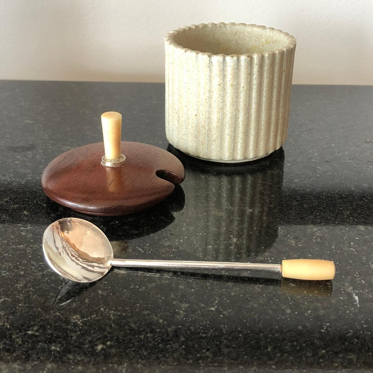 A mustard or jam pot by Arne Bang reeded beige stoneware vessel, with teak cover with silver ring and bone finial, together with a fine sterling silver spoon with bone handle. Signed and numbered with AB monogram and 128 on the base. Beautiful and