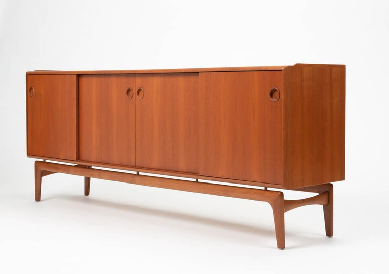 A Danish modern teak credenza or sideboard from Arne Hovmand Olsen for Mogens Kold Møbelfabrik. The piece has four sliding panel doors on two sets of runners, allowing flexibility of access or display. Each door opens at a recessed round pull. The