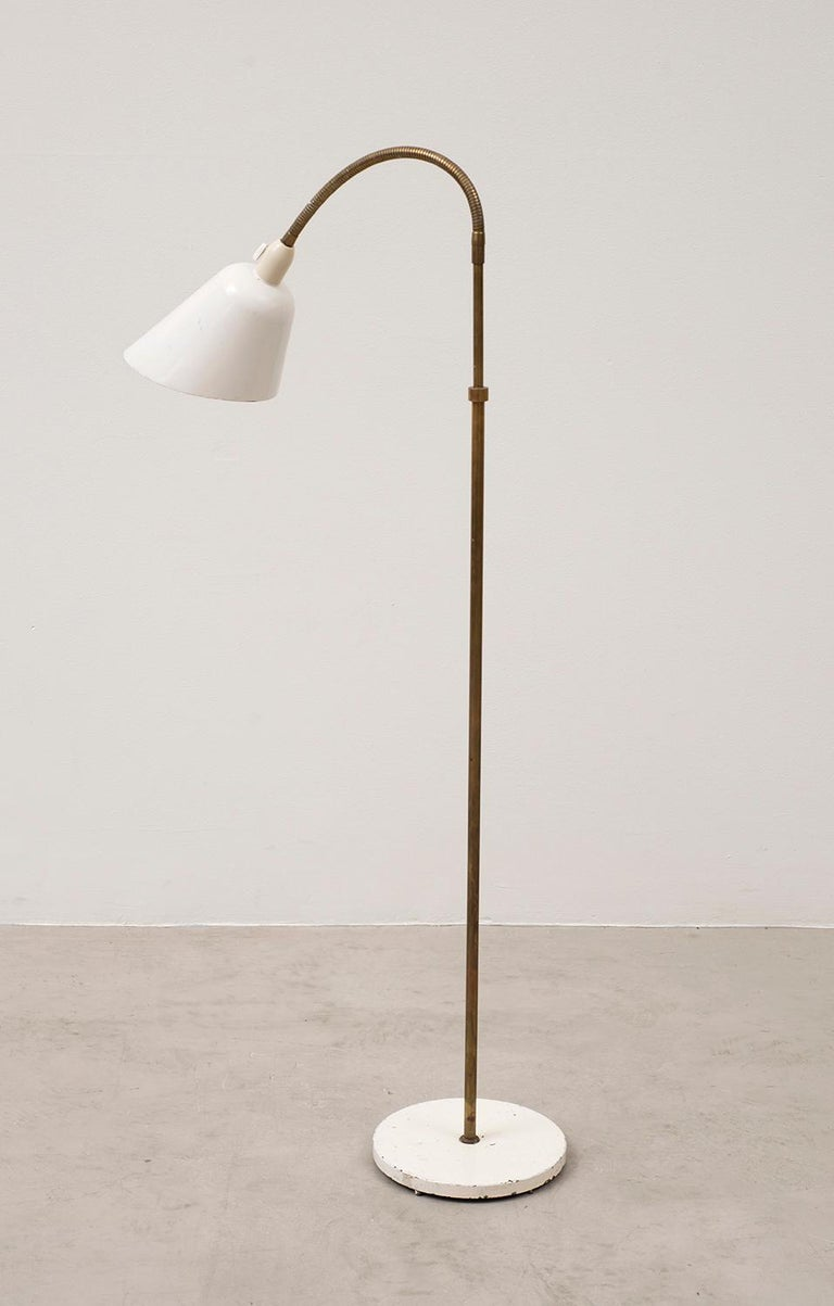 An early floor lamp by Arne Jacobsen in original condition, designed in 1929. Produced by Louis Poulsen in Denmark. Lovely patina on the painted shade and painted metal base. Shaft in original solid brass is adjustable and extends up to 5 feet in