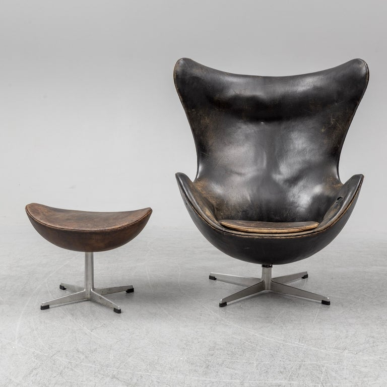 Early easy egg chair model 3316 and ottoman designed by Arne Jacobsen and produced by Fritz Hansen in Denmark in 1958. Vintage original upholstery with patinated dark brown leather. Signed by Fritz Hansen.
