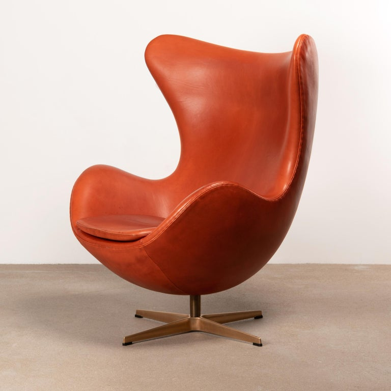 Iconic and beautifull Egg chair designed by Arne Jacobsen for Fitz Hansen in 1958. Original light patined Grace Walnut Leather with base in brown bronze polisehed aluminum with swivel / adjustable tilt function. All in very good original condition.