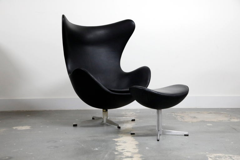 This iconic black leather egg chair by Arne Jacobsen is an all-original 1965 production by Fritz Hansen and signed underneath both pieces with the original date-stamped foil labels. The Classic and timeless (original) black leather is one of the