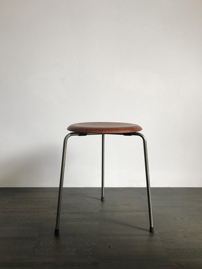 Danish teak stool designed by Arne Jacobsen for Fritz Hansen, first edition with brass dot, 1950s.  Please note that the item is original of the period and this shows normal signs of age and use.