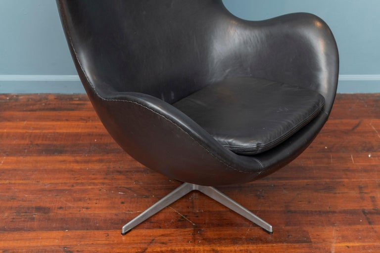 Arne Jacobsen design Egg chair for Fritz Hansen, Denmark. This chair dates from the 1960s and has new foam and upholstered in high quality Italian black leather for my own home about 5 years ago and gently used. Fluted aluminum base shows age