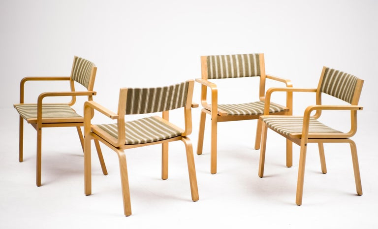 Rare set of four chairs with the original upholstery. Each of the student rooms at St. Catherine College was furnished with an easy chair with frames of laminated wood. These chairs where only made for the St. Catherine College at Oxford, so they