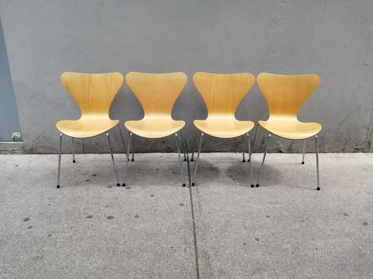 A set of 4 ash plywood and steel model 3107 (number 7) chairs by Arne Jacobsen. These chairs were manufactured in 1999 by Fritz Hansen and distributed by Knoll Studio. The chair's wood structures show lovely veneer grains.  We currently have other