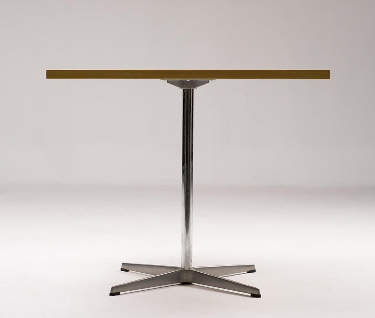 Elegant table designed by Arne Jacobsen and produced by Fritz Hansen in Denmark. This table will serve well as a small cafe style breakfast table or an entry way or game table. Beautiful original ash veneer top on a cast aluminum base. A Jacobsen