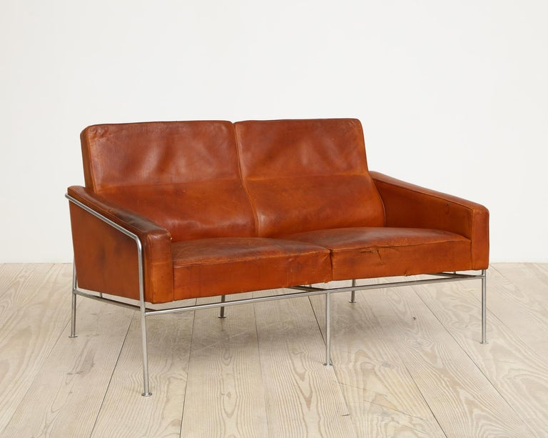 Arne Jacobsen, rare, original production two-seat sofa, model #3302 with original leather, origin: Denmark, 1956, manufactured by Fritz Hansen, leather, bronze-plated steel.  References: Arne Jacobsen, Thau and Vindum, pg. 466.