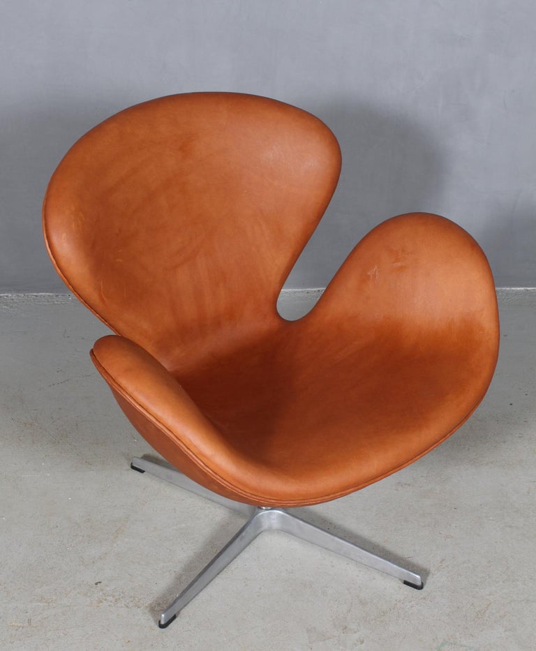The swan chair, new upholstered in cognac aniline leather.   Fritz Hansen. 1981.   Upholstered in Denmark in 2019 with aniline leather.   This iconic chair is one of the most famous chairs in the world and is recognized by design lovers in all