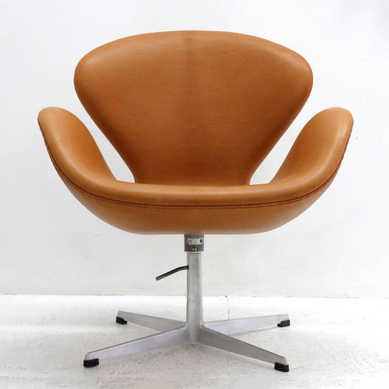 stunning 'Swan' chair, early model 3320, by Arne Jacobsen, lounge chair on a height adjustable four-star aluminum base, upholstered in cognac range aniline leather, originally designed 1957-1958 for the Hotel Royal in Copenhagen, marked Fritz Hansen.