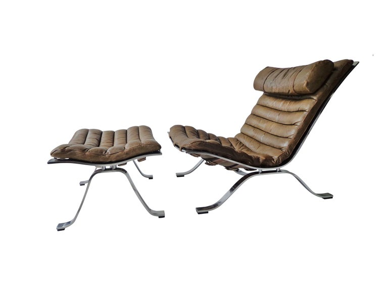 Comfortable lounge chair and ottoman designed by Arne Norell. This award winning lounge chair is made of high quality flat matte-chrome-plated steel and original cognac/brown leather. The set is in beautiful condition with fantastic patina from age