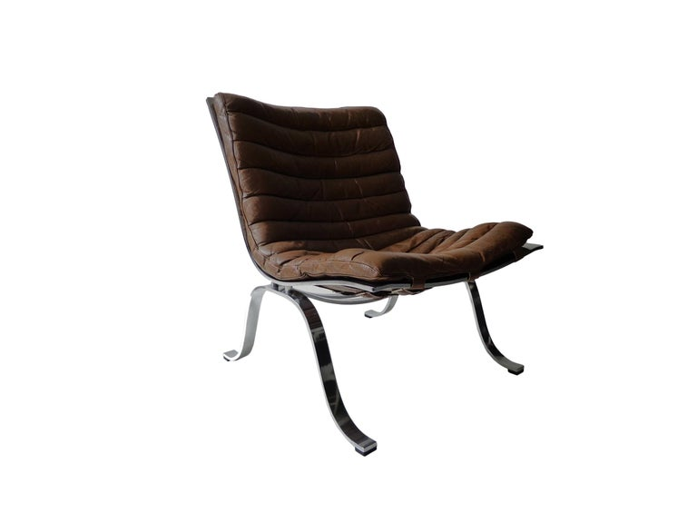 Comfortable 'Ariet' easy chair and ottoman designed by Arne Norell. This easy chair is made of high quality flat matt, chrome-plated steel and original cognac/brown leather. The chair is in beautiful condition with fantastic patina from age and