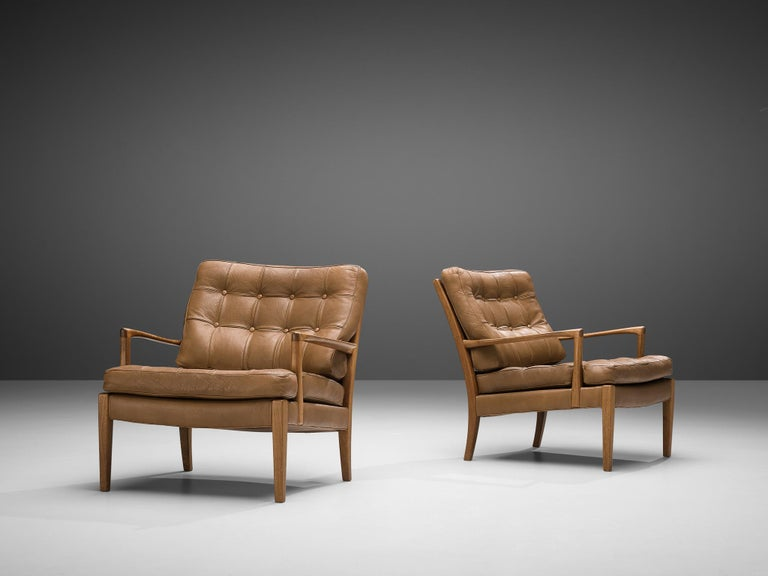 Arne Norell for Møbel AB Sweden, two easy 'Löven' chairs, brown leather, teak, Sweden, 1960s  These chairs are designed by Arne Norell. The pieces are elegant lounge chairs with leather cushions. The teak frame is delicately carved and the set