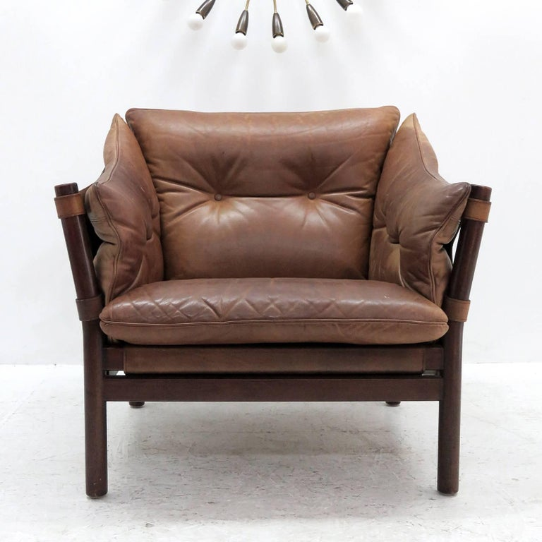 stunning pair of leather armchairs designed in the early 1960s designed and produced by Norell Möbel AB, Sweden, with thick tufted leather cushions on saddle leather sling supports with brass hardware, the frame is made of sturdy, dark stained solid