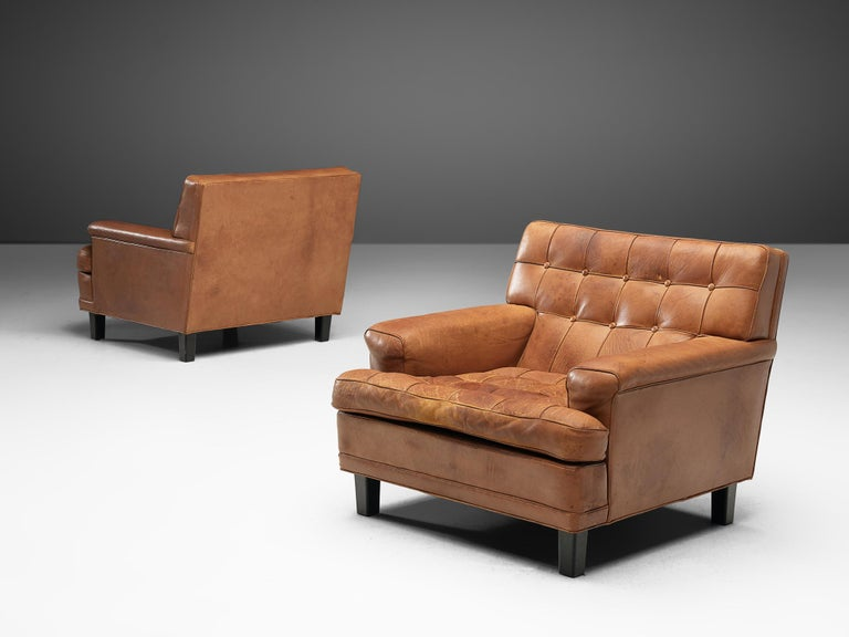 Arne Norell, pair of lounge chairs, in leather and wood, Sweden, 1960s.  Two lounge chairs designed by Arne Norell with wonderful shapes and comfort in cognac leather. The tufted leather cushions give these chairs an interesting appearance. The