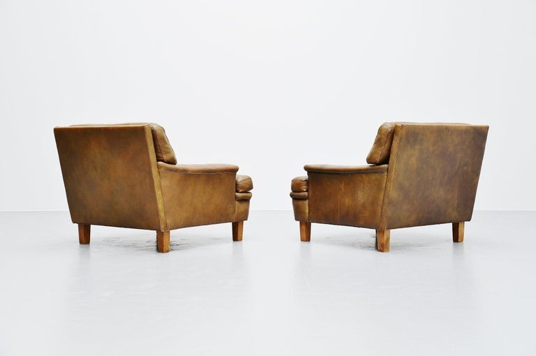 Very nice pair of Merkur lounge chairs designed by Arne Norell and manufactured by Arne Norell AB in Aneby, Sweden, 1960. The chairs have very nice olive green tufted leather cushions with solid oak feet. The chairs seat very comfortable, its a