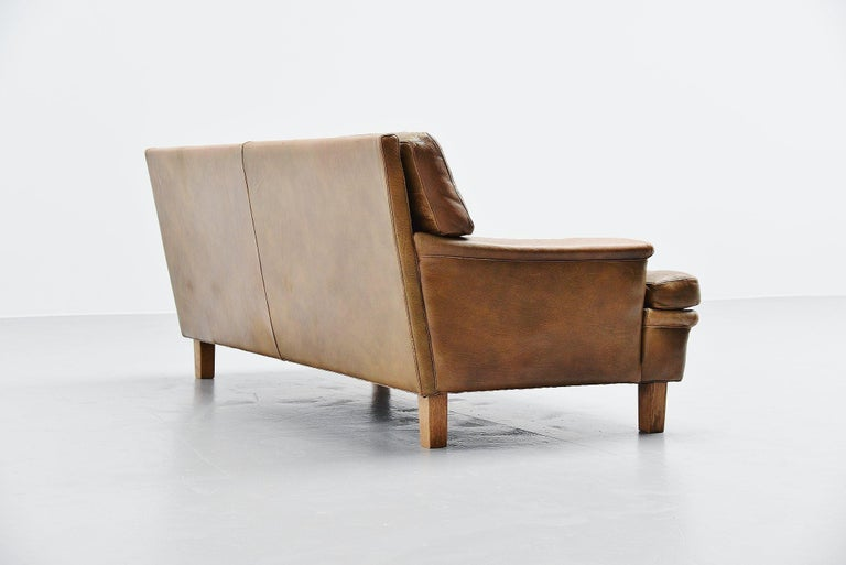 Very nice two-seat Merkur sofa designed by Arne Norell and manufactured by Arne Norell AB in Aneby, Sweden, 1960. The sofa has very nice olive green tufted leather cushions with solid oak feet. The sofa seats very comfortable, its a heavy quality