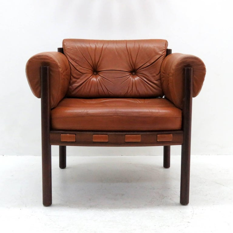 Stunning pair of leather and rosewood armchairs designed in the early 1960s by Arne Norell for Coja Culemborg, with thick tufted cognac colored leather on a sturdy, solid rosewood frame. The chairs are as comfortable as they look.