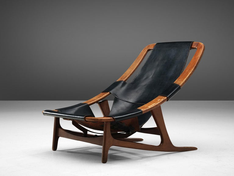 Arne F. Tidemand Ruud for ISA, lounge chair 'Holmenkollen,' teak and light black leather, Italy, 1959.  This easy chair is designed by Norwegian designer Arne F. Tidemand Ruud. This chair is very dynamic due it's design and shapes. The bended teak