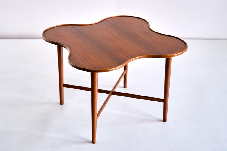 This very rare side table was produced in Denmark in the early 1960s. The design is attributed to Arne Vodder, produced by the manufacturer Bovirke. The quatrefoil shape of the top, executed in a beautifully veneered teak wood, gives the table a