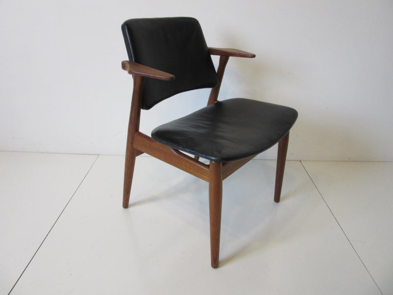 A dark teakwood chair with smaller upper arm rests and satin black leather seat and back rest still retains the original upholstery and manufactures branded mark. George Tanier Selections - Helge Sibast Made in Denmark makes a great living area or