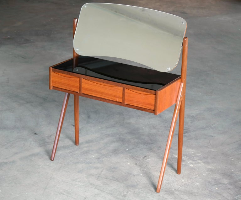 Very elegant vanity or small dressing table designed by Arne Vodder in Denmark in the 1960s. Cabinet made from dark teak and the drawer fronts in light colored teak veneers creating a nice two-tone - topped with a black glass top over three drawers