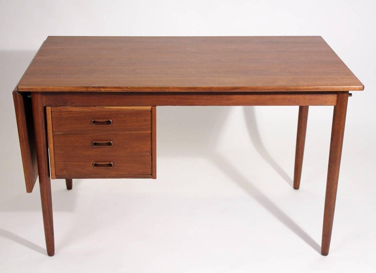 Beautiful teak wood Danish drop-leaf expandable desk designed by Arne Vodder. The desk has a drop leaf that can be used for more room. Drawers can be moved from side to side so you can move your chair to either side. Great design. Desk has wonderful