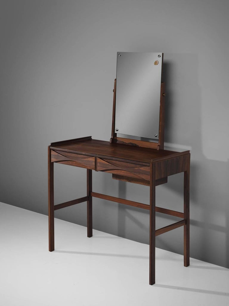 Arne Vodder, dressing table, rosewood, mirror, Denmark, 1950s.  This refined, delicate dressing table is designed by Arne Vodder. The piece features the quintessential bow tie grips that is Vodder's trademark. The piece holds several details that