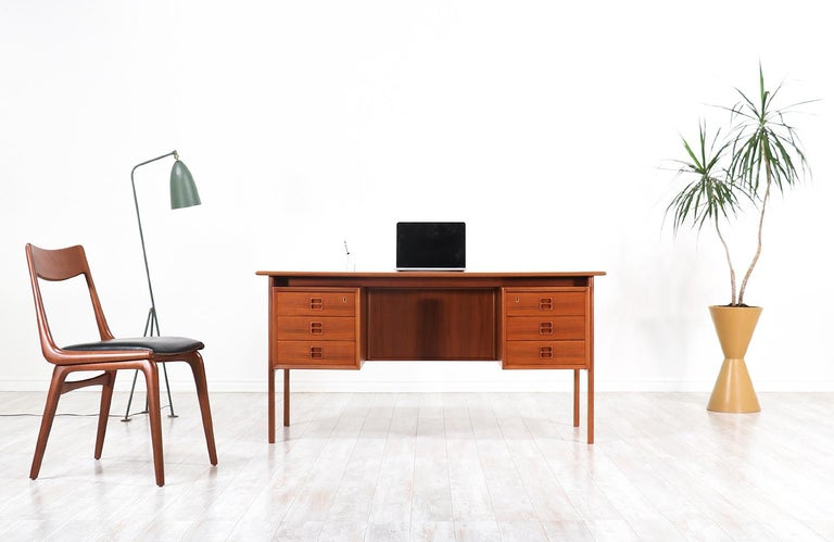 Elegant modern executive desk designed by Arne Vodder for Sibast in Denmark, circa 1950s. This striking design features a teak wood frame with three spacious drawers on each side and an open bookshelf in the back for additional storage and display