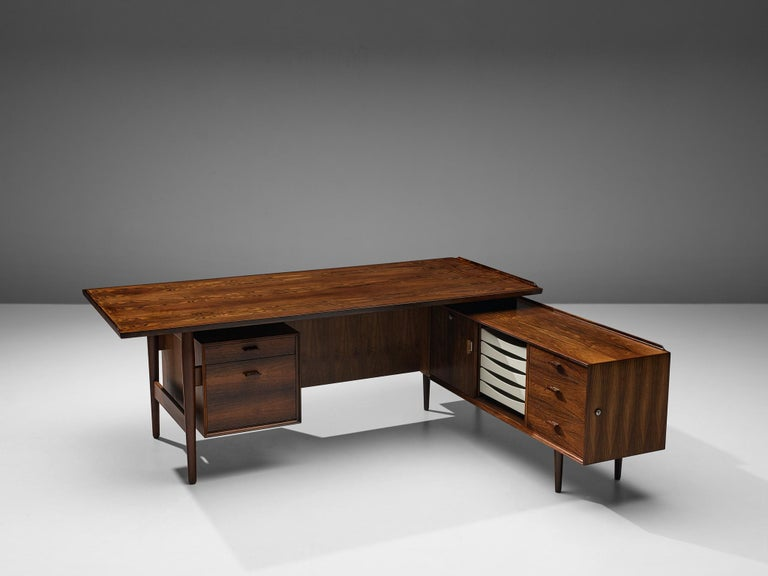 Arne Vodder for Sibast, corner desk, rosewood, Denmark, 1950s  Danish designer Arne Vodder created this functional, free-standing corner desk for Sibast. Rosewood with its beautiful natural grain gives this pieces a luxurious look. The desk with
