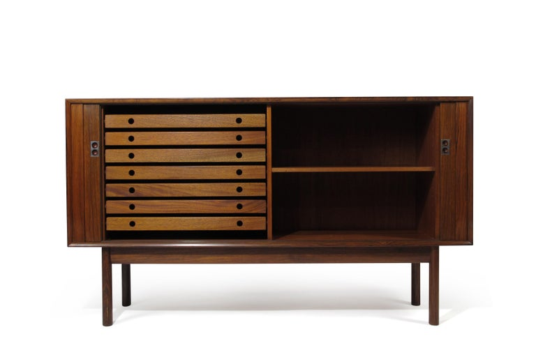 Arne Vodder for Sibast rosewood credenza with mitered corners, sliding tambour doors and metal pulls. The interior features a mahogany interior with adjustable shelf and seven silverware drawers. The cabinet has been lightly restored and in good