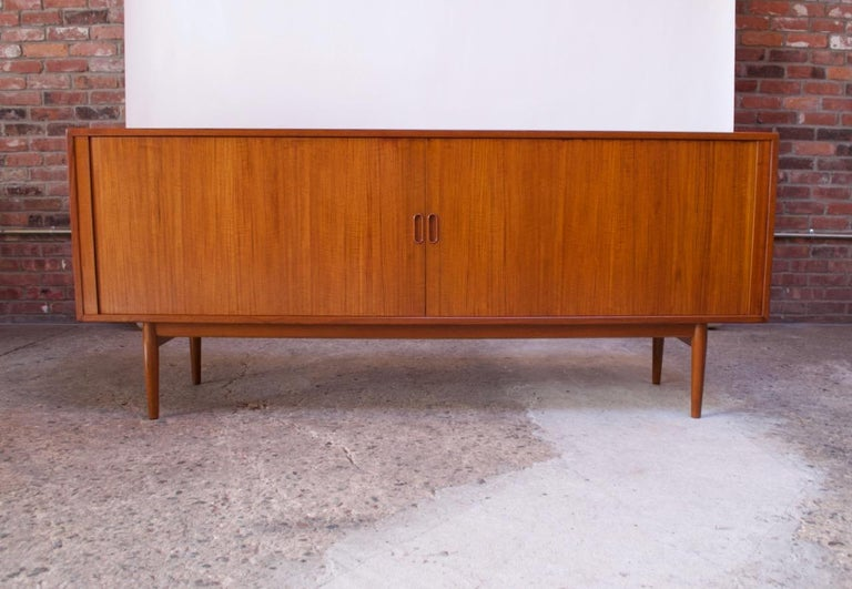 1950s Danish modern teak credenza (model 37) designed by Arne Vodder for Sibast Møbler. Composed of a teak frame with two tambour doors with recessed pulls that slide open to reveal a total of four adjustable shelves (three shorter on the right side