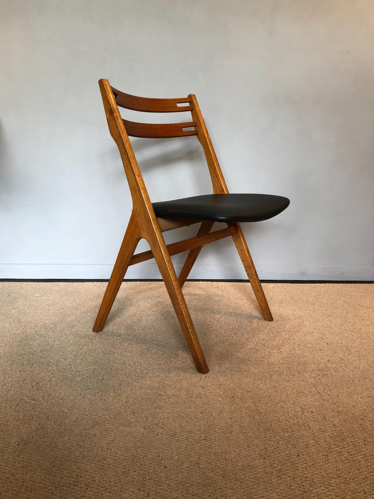 A set of six oak dining chairs designed by Arne Vodder for Sibast, Denmark, circa 1960. Re-oiled frames with newly upholstered black leather seats. Original Sibast labels still intact underneath. Fabulous Midcentury walking leg design saw back