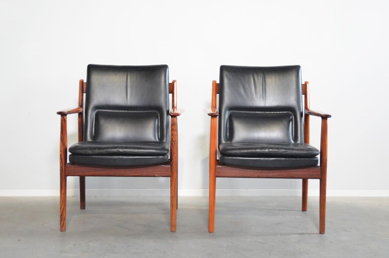 Comfortable rosewood armchairs by Arne Vodder with a with black leather upholstery. The backrest has a built-in extra support for the lower back. The upholstery is original and in very good condition. The chairs are marked under the seating.