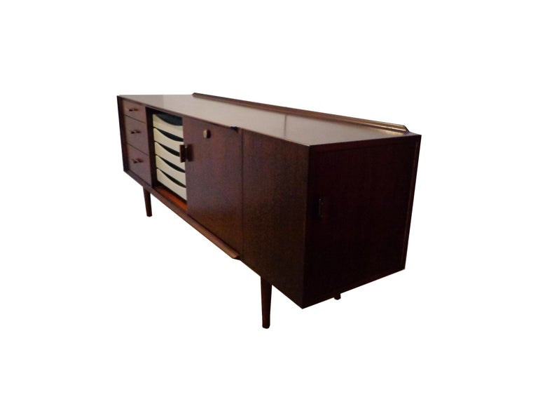 Arne Vodder freestanding sideboard in Brazilian rosewood, top with profiled back edge. Front with three drawers, sliding door and five white coloured pull out trays. Handle with metal detail. Key included.