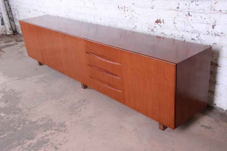 An outstanding 10 foot monumental Danish modern teak sideboard credenza or bar cabinet  In the manner Arne Vodder  Denmark, circa 1960s  Teak, with bronzed metal legs and mirrored glass bar cabinet interior.  Measures: 118.25