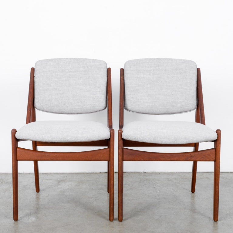 A stylish pair of wooden chairs from Danish furniture designer Arne Vodder. Vodder's past work designing homes is on display in the architectural lines of these chairs, in the rear supports that rise up like flying buttresses, adding support and