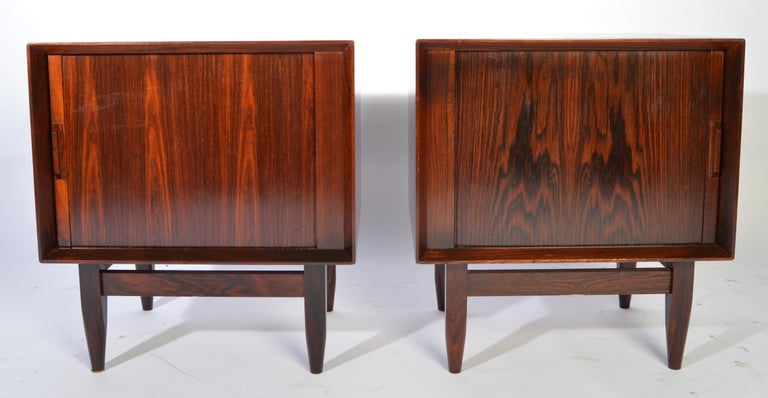 Arne Wahl Iversen Brazilian rosewood nightstands having tambour doors that reveal a top drawer and shelved lower case storage. Outstanding overall condition. Masterfully refinished, circa 1960.