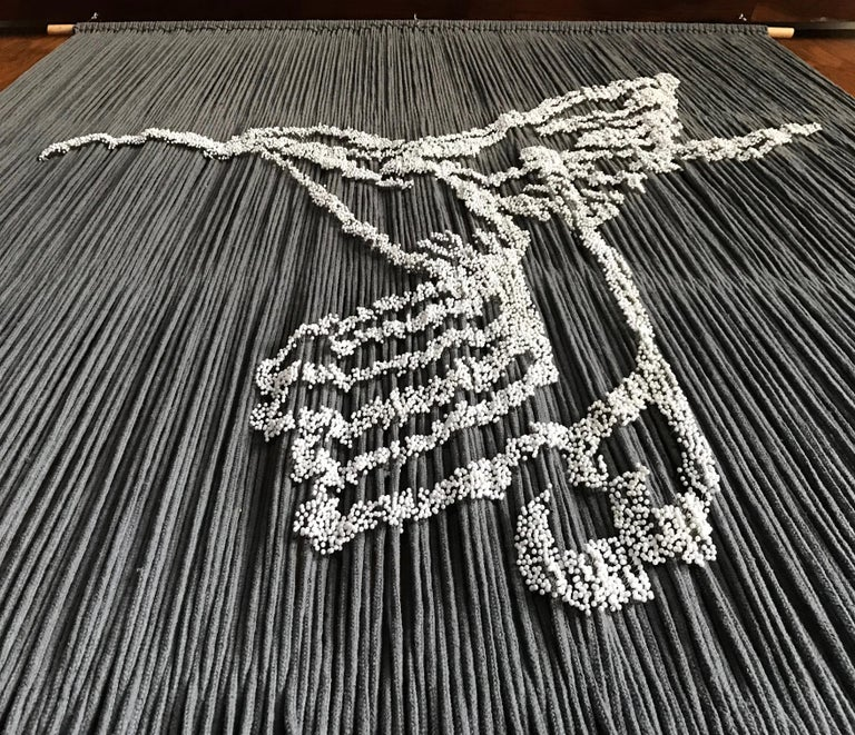 This work of art is all hand made with more than 17,000 pins delicately inserted with resin onto hanging gray ropes. The two colors chosen give this lovely work an elegant feeling to spaces.   Inspiration came from the Aztec god of war,