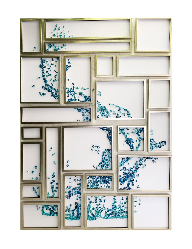 Hand made elegant wáter sculpture collage for walls. This is all made with 10,520 buttons and nails all delicately placed upon a white canvass with a silver frame. The blue tones and acrylic pieces give subtle reflections to the piece. This wáter