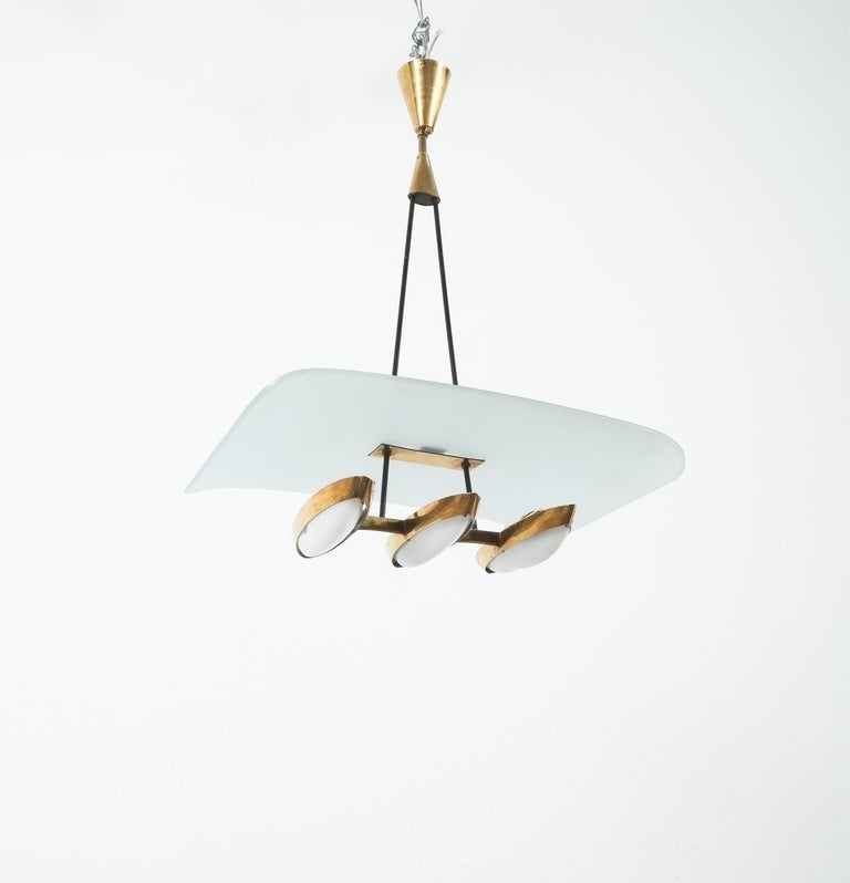 Chandelier from frosted glass and brass attributed to Stilnovo, Italy, circa 1954  Rare suspension chandelier with floating frosted light-blue glass diffuser and three polished brass up-lights with perspex lenses. The lenses show heat-inflicted