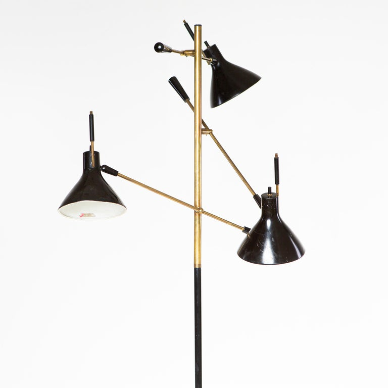 Large floor lamp standing on a round marble base with black shaft and three brass arms. These are adjustable in inclination and end in conical black lampshades. Labeled