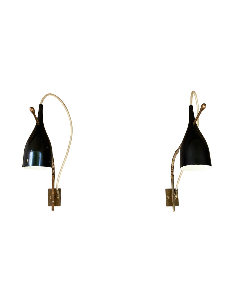 Rare wall sconce, Lucinella model number 14140, by Angelo Lelii (Lelli) for his company, Arredoluce, 1950.   Structure compromised of flexible stem and wall plate in brass. Visibly encased electric wire in flexible tandem. Shades are in black