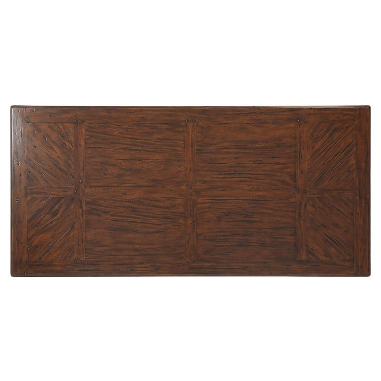 An antiqued mahogany monastery dining table, the planked top with chevron parquetry ends, on rafter end supports joined by a Union stretcher. Inspired by an Arts & Crafts original.  Dimensions: 84