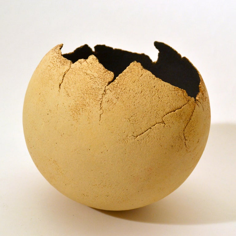 Sculptural round studio pottery decorative abstract bowl by unknown artisan producing this unique Raku fired ball shaped vessel, black inside and unglazed cream outside with the edges as a delicate broken egg shell. The studio potter is one who is a