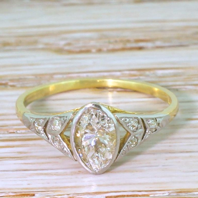 A marquise cut diamond ring of undeniable beauty. The slightly rugby-ball shaped old marquise cut – bright and internally clean – is rubover in 18k white gold. The vented, white gold shoulders feature a double-split, with each half set with an old